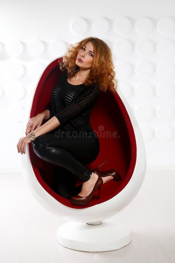 Giovane donna sexy della testarossa in uovo-sedia immagine stock libera da diritti