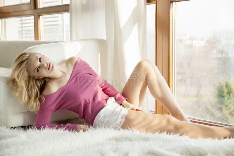 Giovane donna sexy esile in maglione rosa contro la finestra fotografia stock