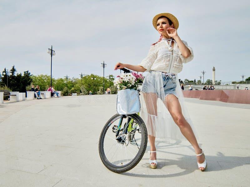 Giovane donna sexy graziosa che posa con una bici fotografie stock