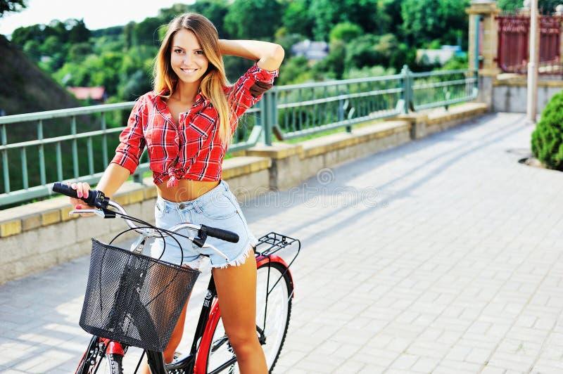 Giovane donna sexy su una posa della bicicletta all'aperto immagine stock libera da diritti