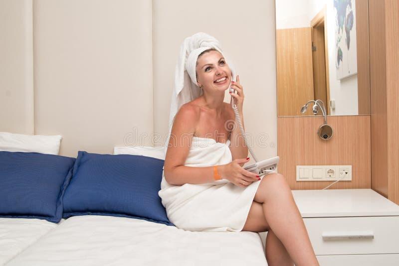 Giovane donna sexy in una camera di albergo che parla sul telefono cellulare fotografia stock