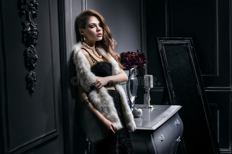 Giovane donna sexy in vestito nero e rivestimento bianco della pelliccia fotografia stock
