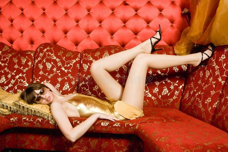 Giovane donna sexy in vetri che pongono sullo strato fotografie stock libere da diritti