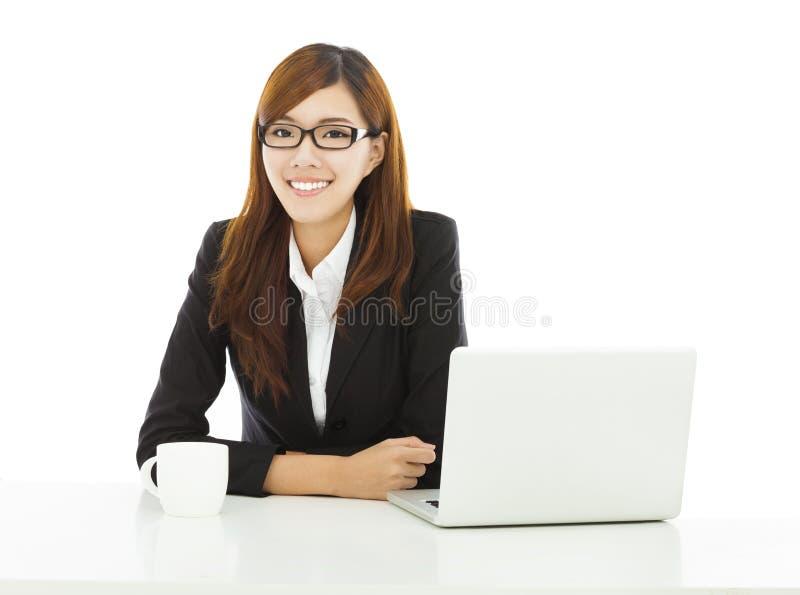 Giovane donna sicura di affari che si siede con il computer portatile immagine stock