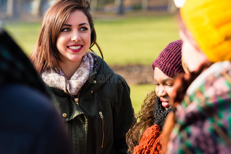 Giovane donna sicura di sé circondata dagli amici all'aperto fotografia stock