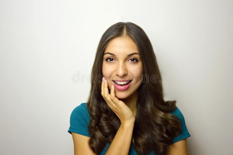Giovane donna sicura felice con il fronte che riposa in sua mano che esamina macchina fotografica con fondo bianco fotografie stock libere da diritti