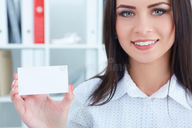 Giovane donna smilling che mostra il segno in bianco vuoto della carta di carta con lo spazio della copia per testo fotografia stock