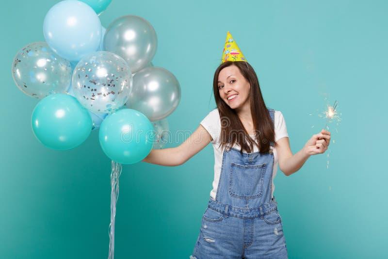 Giovane donna smirking sorridente in cappello di compleanno che tiene stella filante bruciante e che celebra con gli aerostati va immagini stock libere da diritti