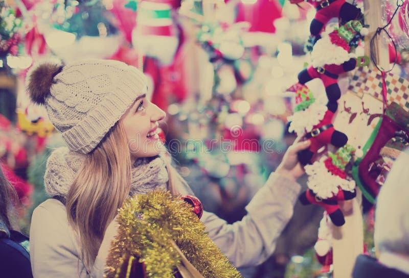 Giovane donna soddisfatta positiva al contatore vicino giusto con Christm fotografia stock libera da diritti