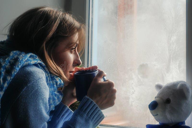 Giovane donna sola di ribaltamento triste bella in maglione che sogna vicino alla finestra congelata immagine stock libera da diritti