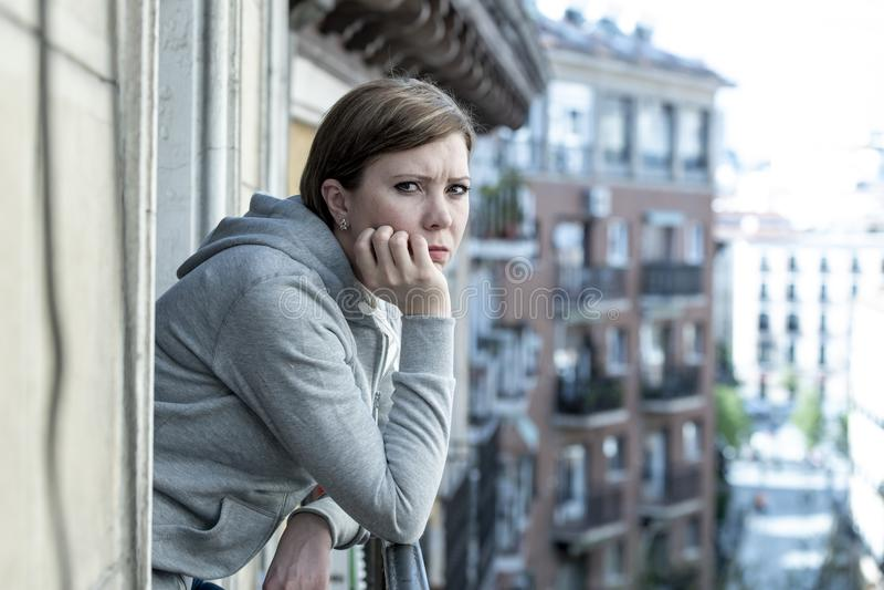 Giovane donna sola infelice attraente che soffre dalla depressione che sembra triste sul balcone a casa immagini stock libere da diritti