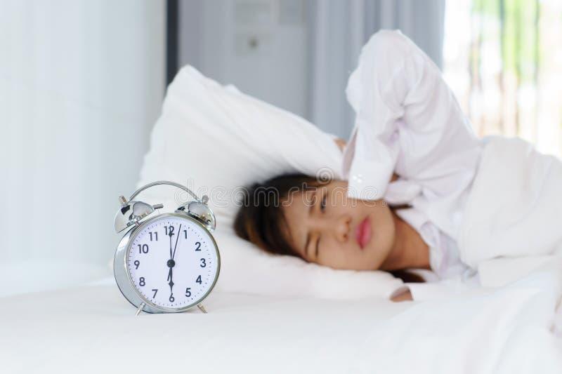 Giovane donna sonnolenta che esamina sveglia con le mani che coprono lui immagine stock libera da diritti