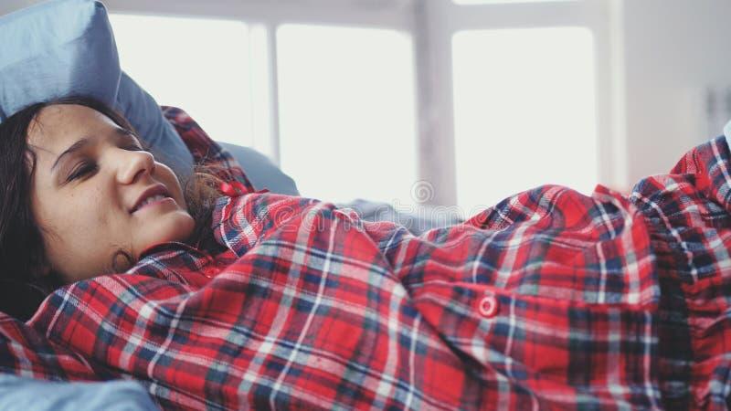 Giovane donna sonnolenta che si trova a letto svegliando e sorridendo sul fondo vago della finestra immagini stock libere da diritti