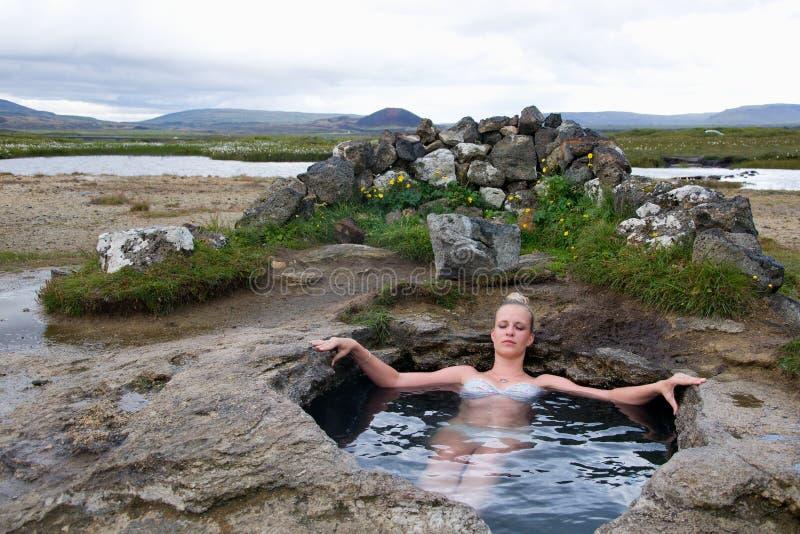 Giovane donna in sorgente di acqua calda naturale in Islanda immagine stock