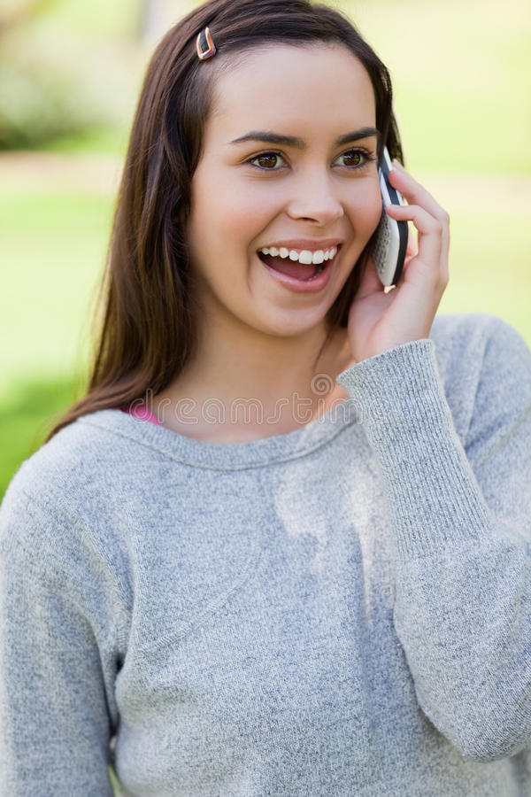 Giovane donna sorpresa che comunica sul telefono immagine stock libera da diritti