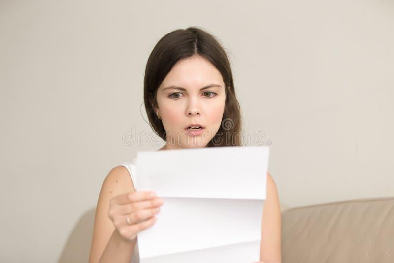 Giovane donna sorpresa che legge lettera inattesa immagine stock libera da diritti