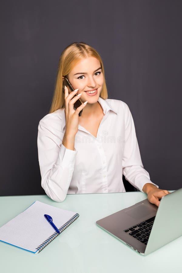 Giovane donna sorridente allegra che ha conversazione dal telefono in ufficio fotografia stock libera da diritti