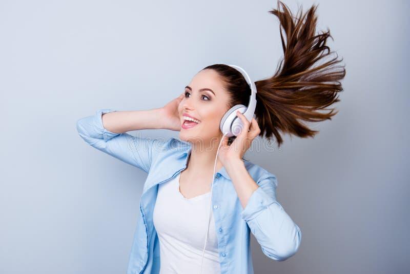 Giovane donna sorridente allegra nell'ascoltare blu la musica un headp fotografie stock libere da diritti