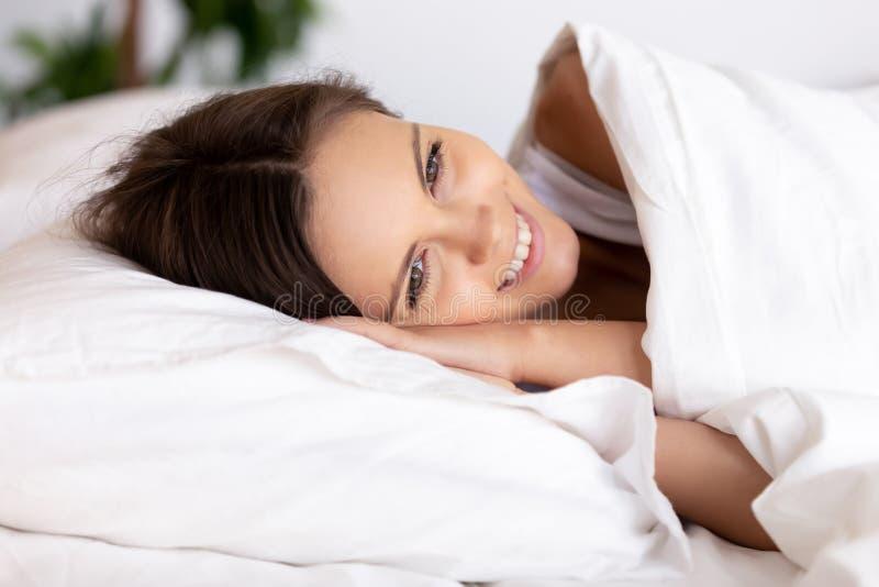 Giovane donna sorridente attraente che si trova nel letto comodo sotto la coperta immagini stock libere da diritti