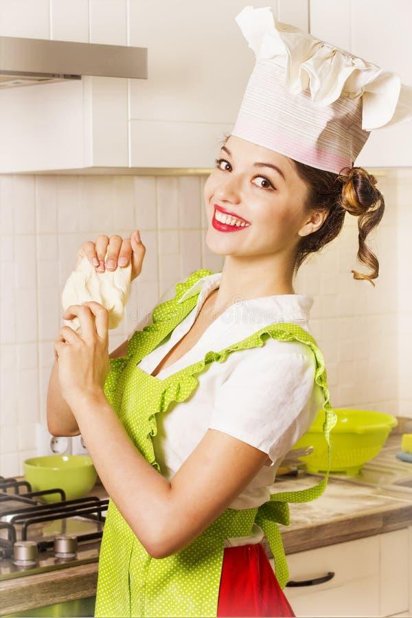 Giovane donna sorridente in cappello del cuoco unico che cucina pasta immagini stock