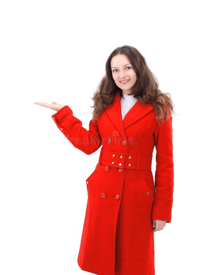 Giovane donna sorridente in cappotto rosso che mostra sullo spazio della copia fotografia stock