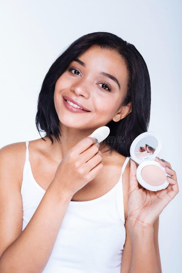Giovane donna sorridente che applica polvere con un soffio fotografia stock