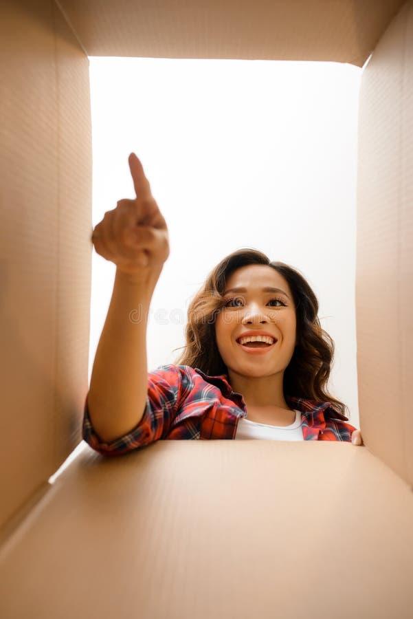 Giovane donna sorridente che apre un contenitore, una rilocazione e un unpacki di cartone fotografia stock