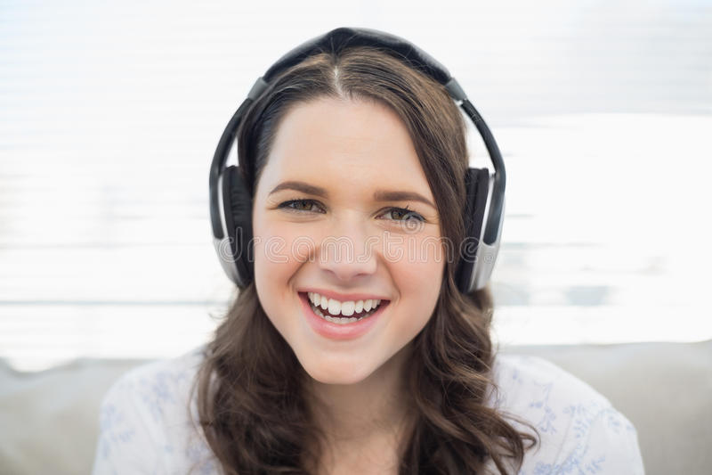 Giovane donna sorridente che ascolta la musica immagini stock