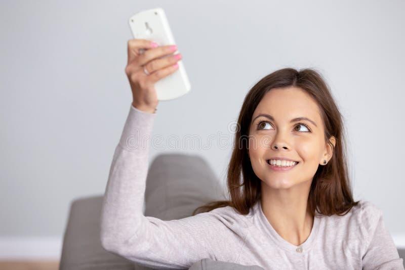 Giovane donna sorridente che consuma fine a distanza del regolatore del condizionatore d'aria immagini stock