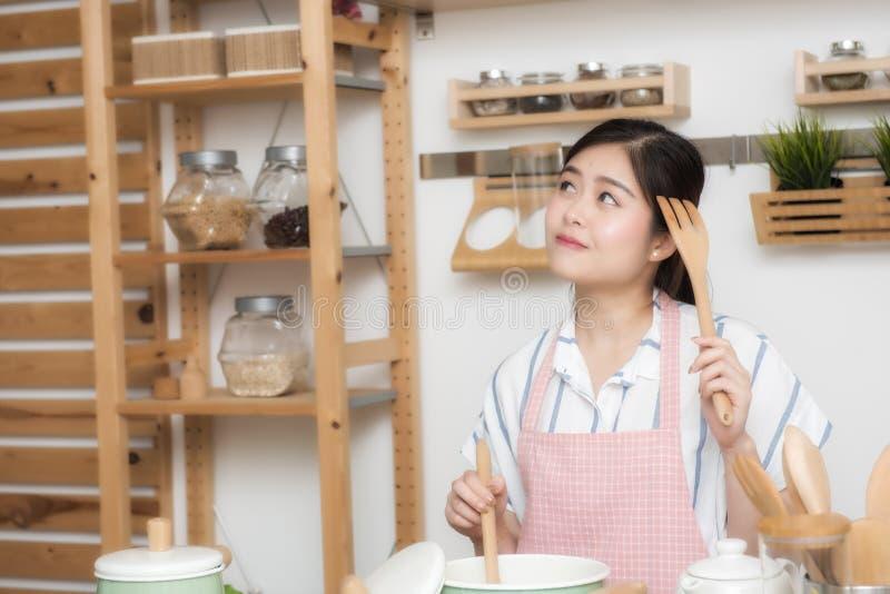 Giovane donna sorridente che cucina nella cucina Alimento casalingo Dieta Concetto stante Stile di vita sano Cottura nel paese pr immagine stock
