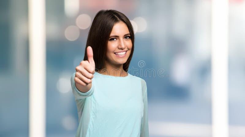 Giovane donna sorridente che dà i pollici in su fotografie stock