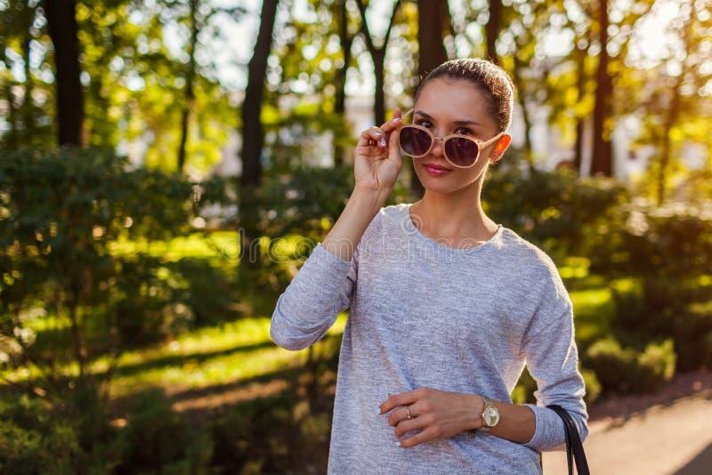 Giovane donna sorridente che decolla i suoi occhiali da sole in parco Bella ragazza con trucco naturale che esamina macchina foto immagini stock libere da diritti