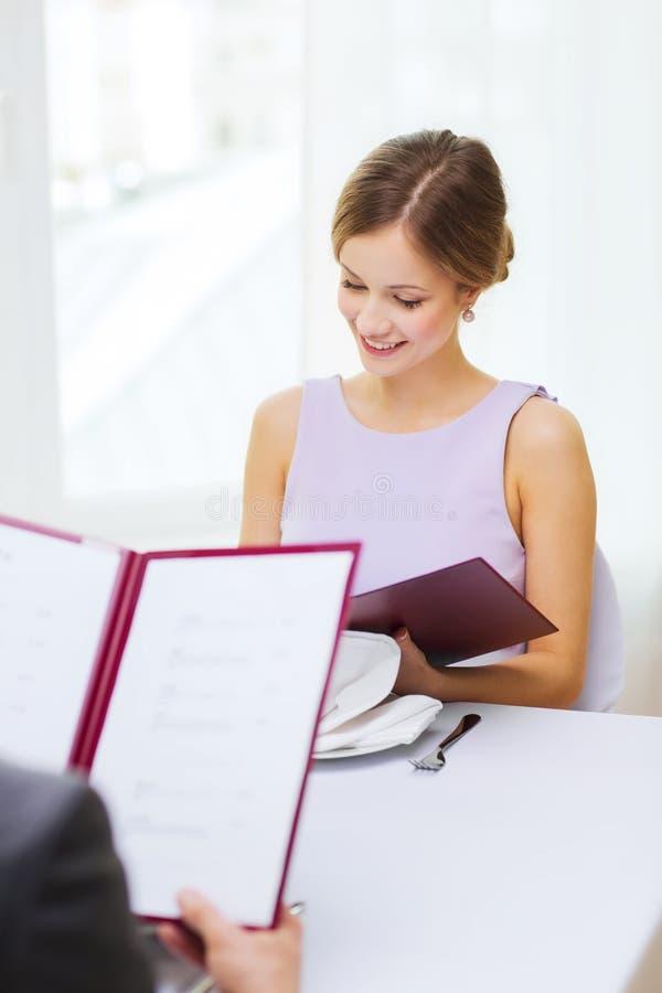 Giovane donna sorridente che esamina menu il ristorante immagine stock
