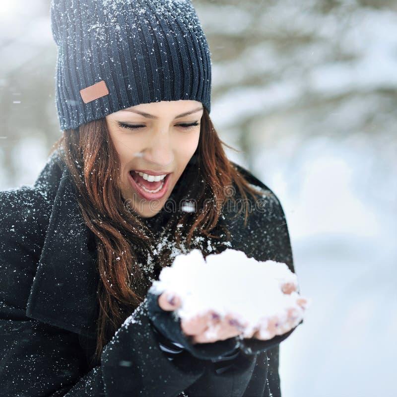 Giovane donna sorridente che gioca con la neve nel parco di inverno fotografia stock libera da diritti