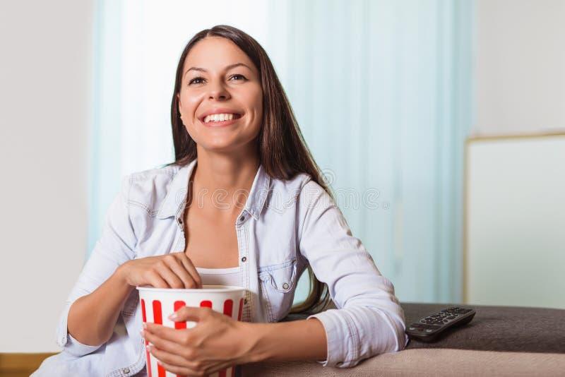 Giovane donna sorridente che guarda un film e che mangia popcorn immagine stock libera da diritti