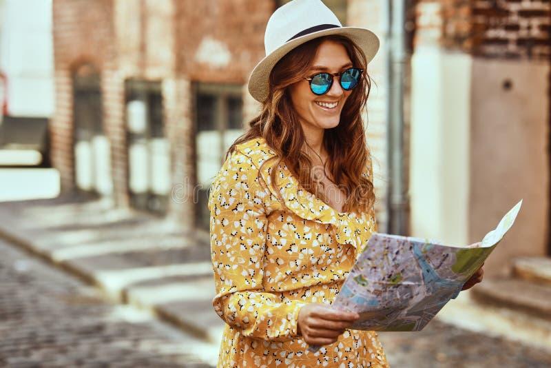 Giovane donna sorridente che legge una mappa mentre esplorando la st del ciottolo fotografie stock