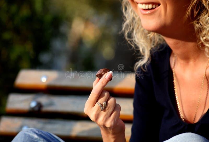 Giovane donna sorridente che mangia cioccolato fotografia stock