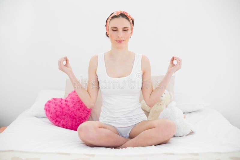Giovane donna sorridente che medita con gli occhi chiusi fotografie stock libere da diritti