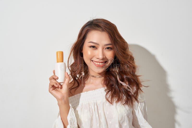 Giovane donna sorridente che mostra i prodotti dello skincare fotografie stock libere da diritti