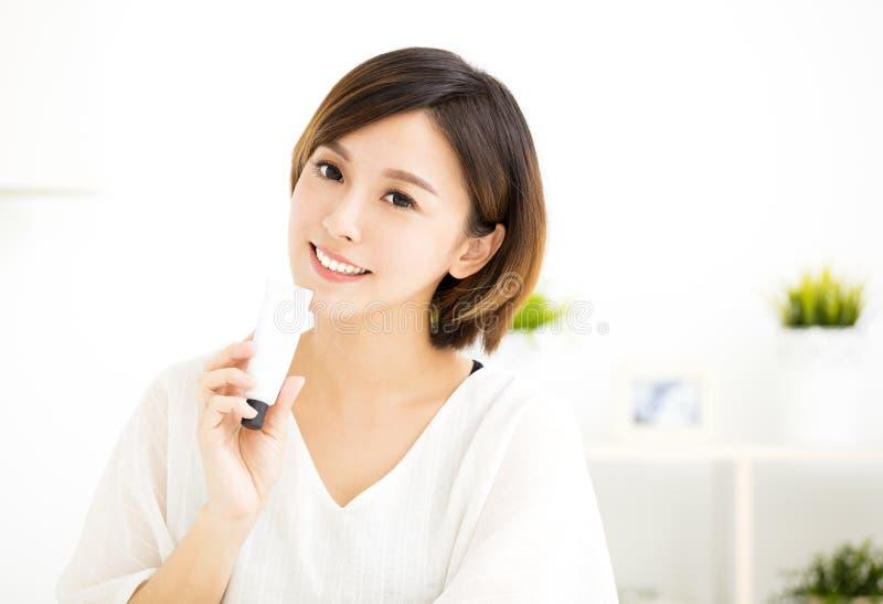Giovane donna sorridente che mostra i prodotti dello skincare fotografia stock