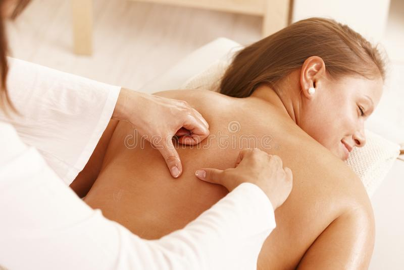 Giovane donna che ottiene massaggio posteriore immagini stock
