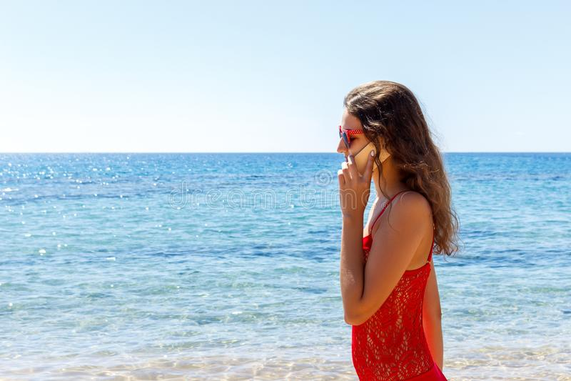 Giovane donna sorridente che parla dal telefono su una spiaggia fotografie stock libere da diritti