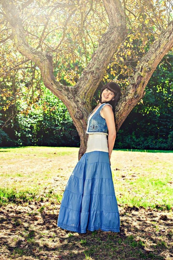 Giovane donna sorridente che pende contro l'albero fotografie stock libere da diritti