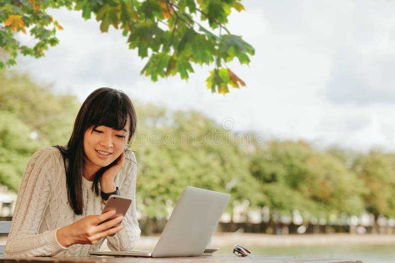 Giovane donna sorridente che per mezzo del telefono cellulare al caffè all'aperto fotografia stock