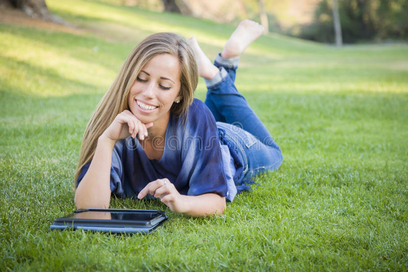Giovane donna sorridente che per mezzo della compressa del computer all'aperto fotografia stock