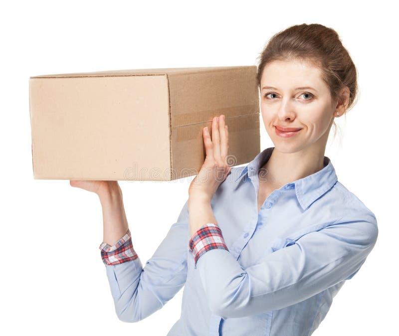 Giovane donna sorridente che porta una grande scatola immagini stock