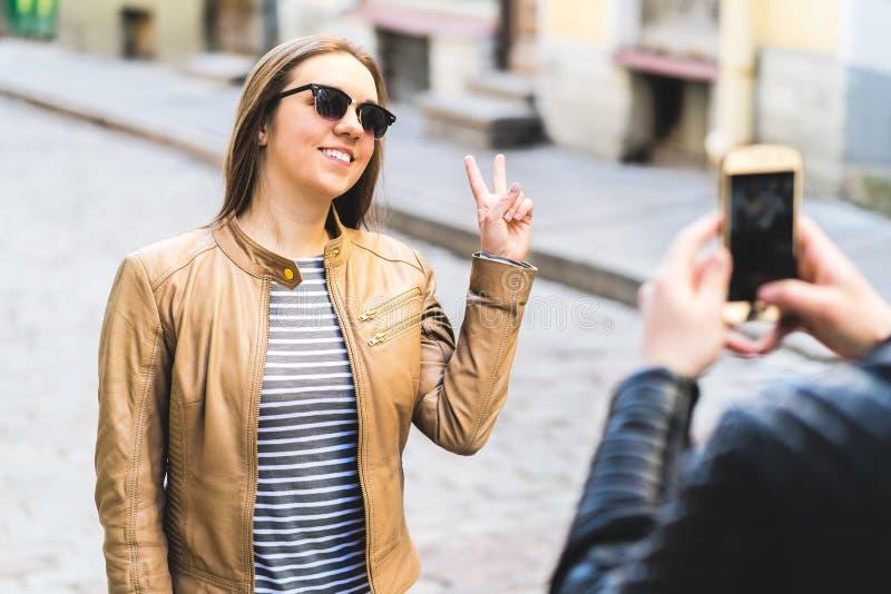 Giovane donna sorridente che posa per il telefono della macchina fotografica fotografie stock libere da diritti