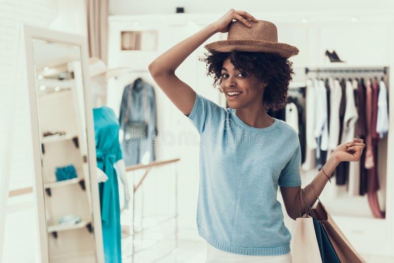Giovane donna sorridente che prova sul nuovo cappello in deposito fotografie stock