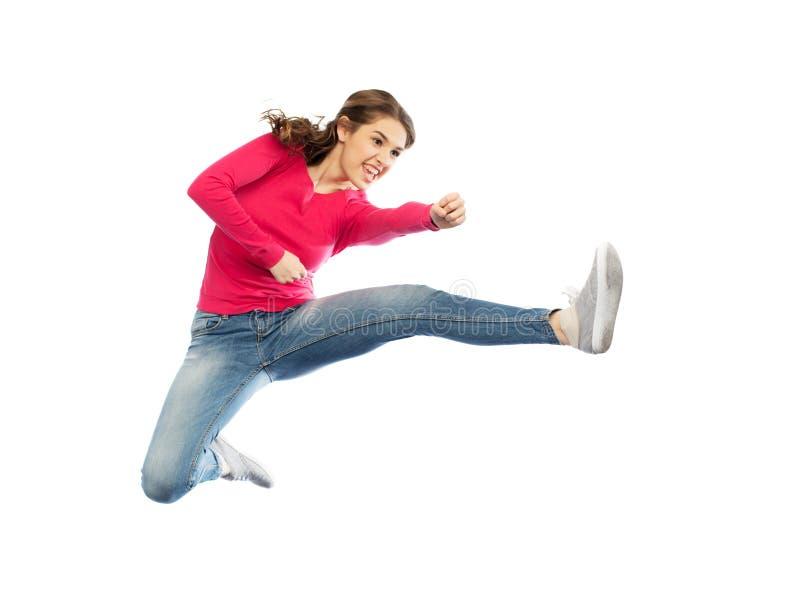 Giovane donna sorridente che salta in aria fotografia stock libera da diritti