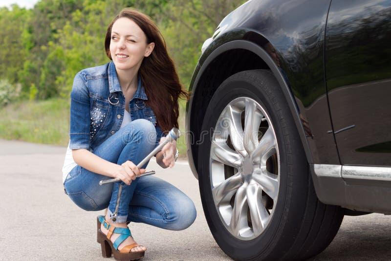 Giovane donna sorridente che si prepara per cambiare un pneumatico fotografia stock